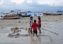 Barn leker på stranden som överallt i världen